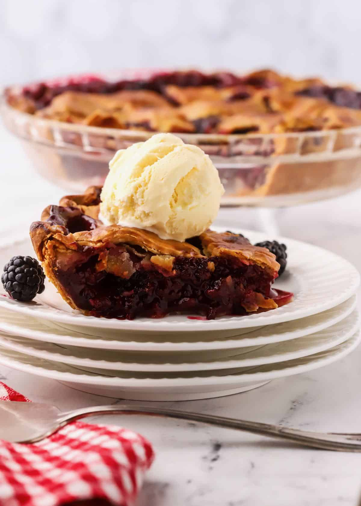 A slice of blackberry pie topped with a scoop of vanilla ice cream.