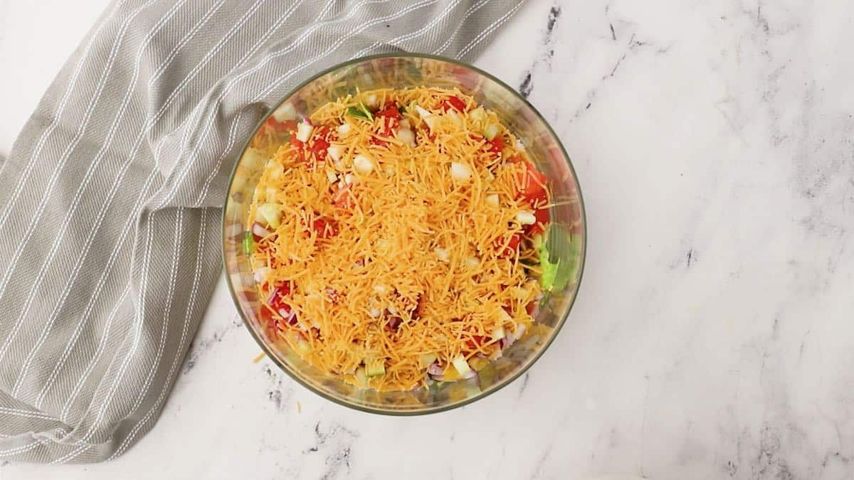 A layer of shredded cheese over lettuce and other ingredients in a trifle dish.