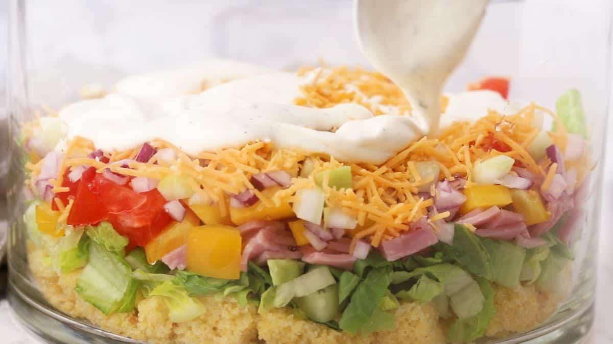 Adding ranch dressing to Cornbread Salad.