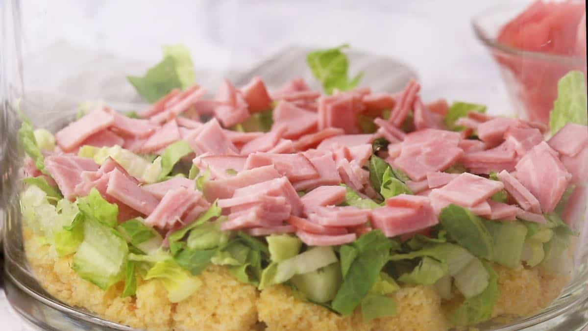 A layer of chopped ham over lettuce in a trifle dish.