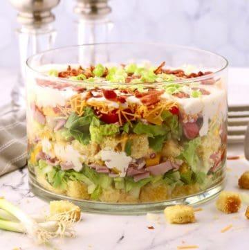 A glass trifle dish with a layered cornbread salad.
