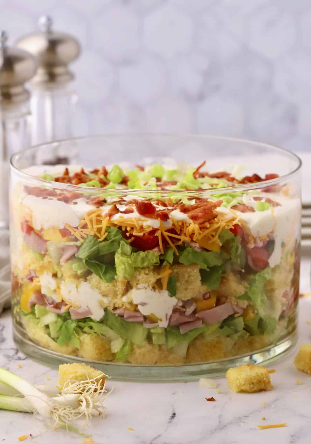 Cornbread salad with layers of vegetables and lettuce.