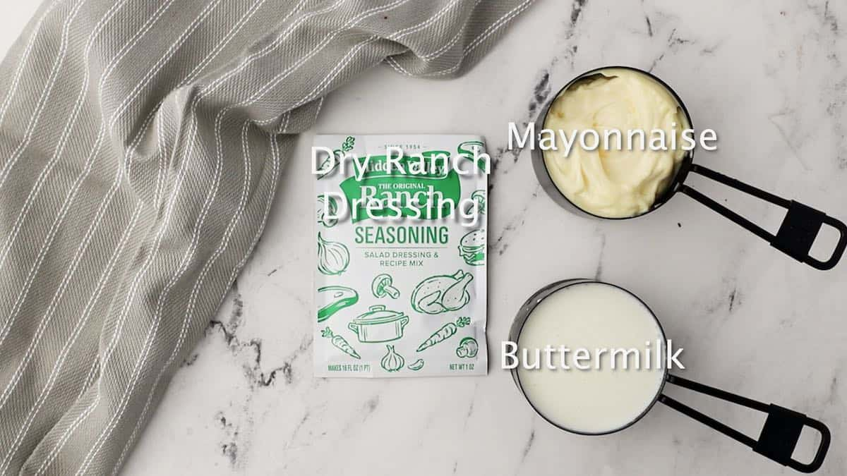 A package of dry ranch dressing, buttermilk,  and mayonnaise.