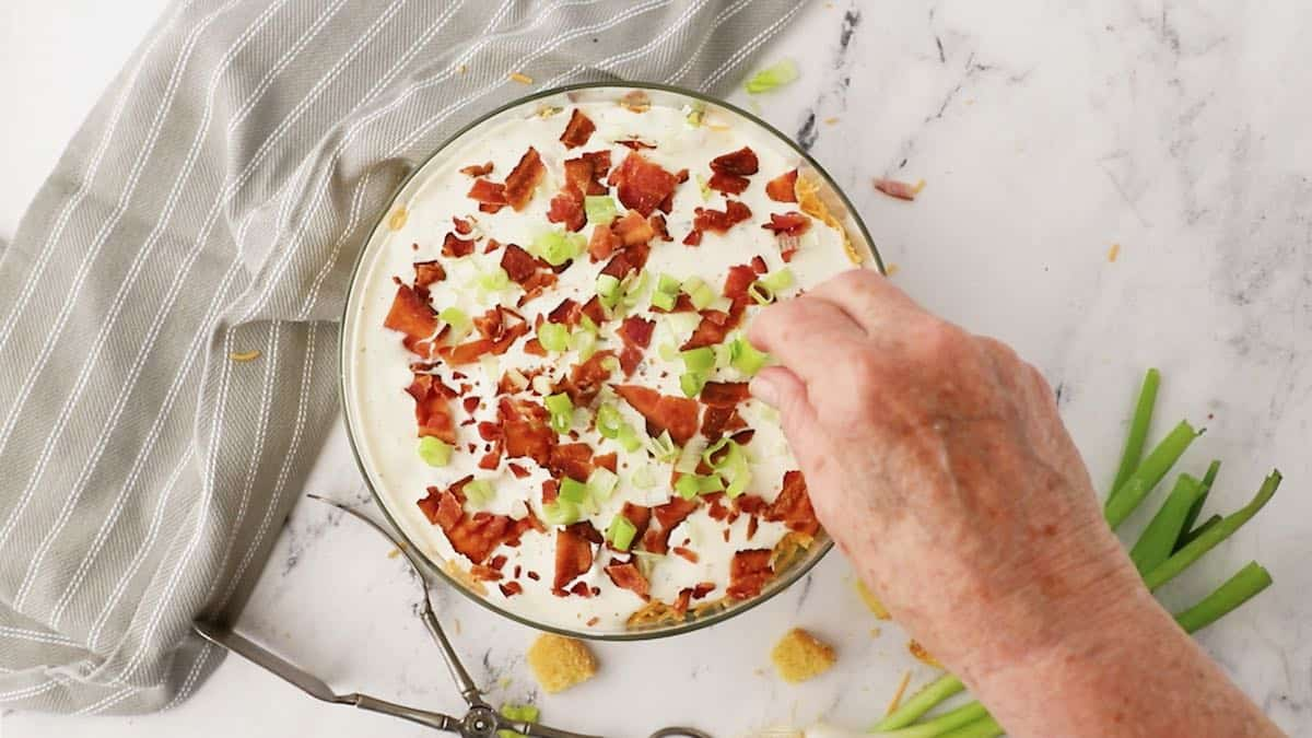 Adding chopped bacon and scallions to the top of a salad.