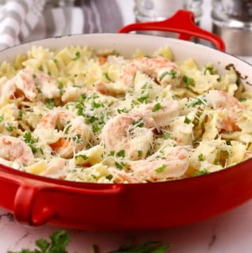 A red baking dish with shrimp pasta garnished with parsley.