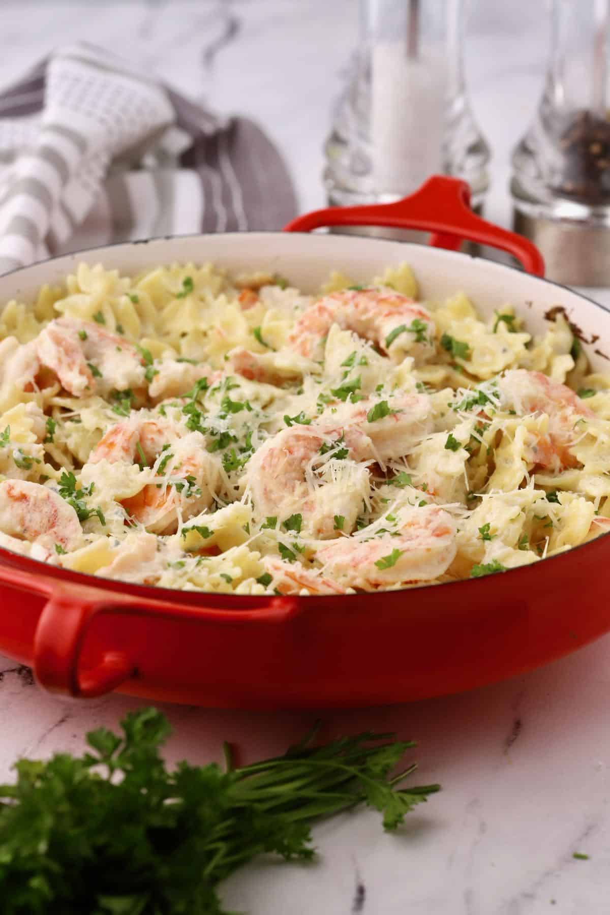 A baking dish full of shrimp pasta with blue cheese.