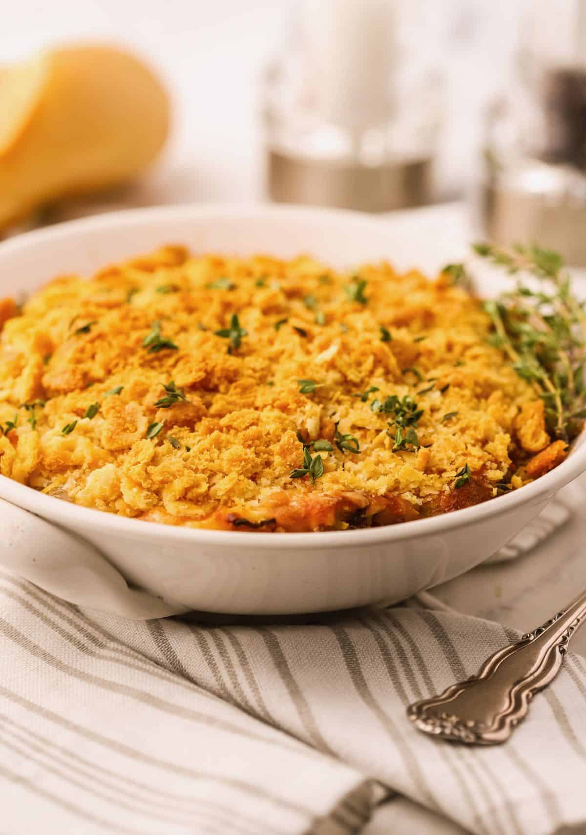 Onion casserole in a white baking dish garnished with thyme leaves.