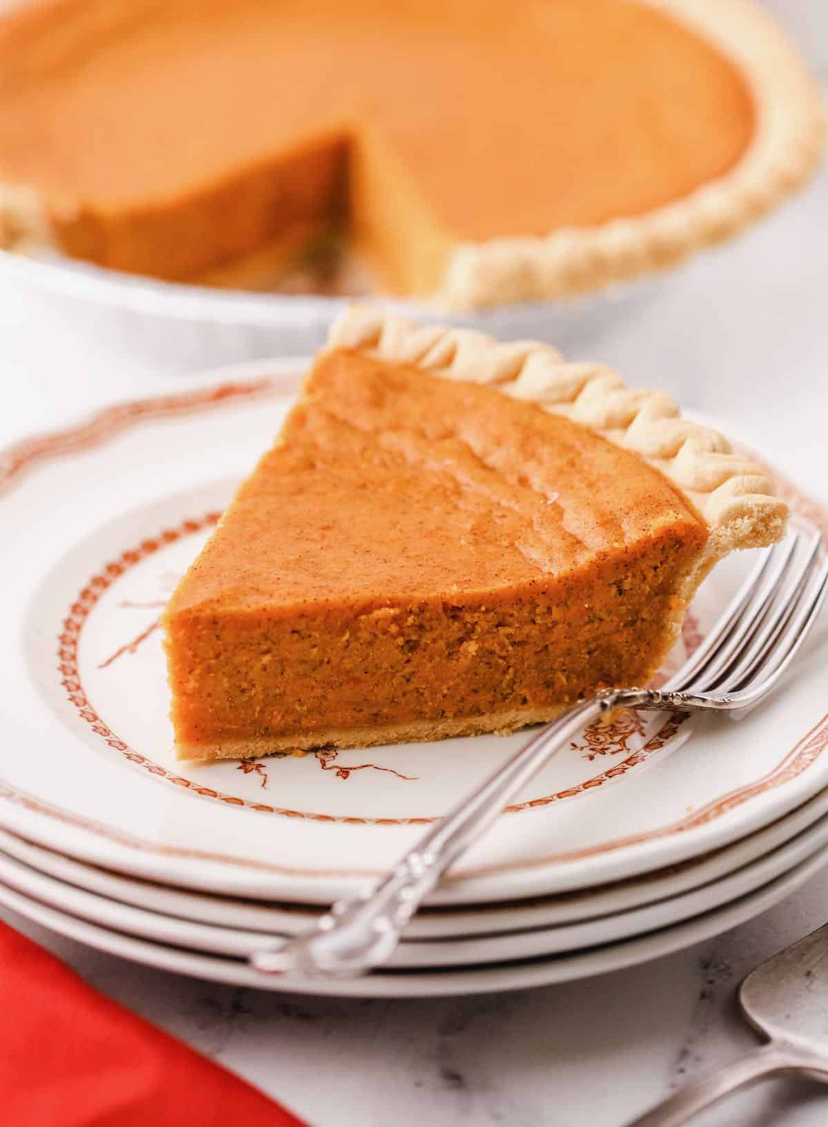 A slice of sweet potato pie on a plate with a fork.