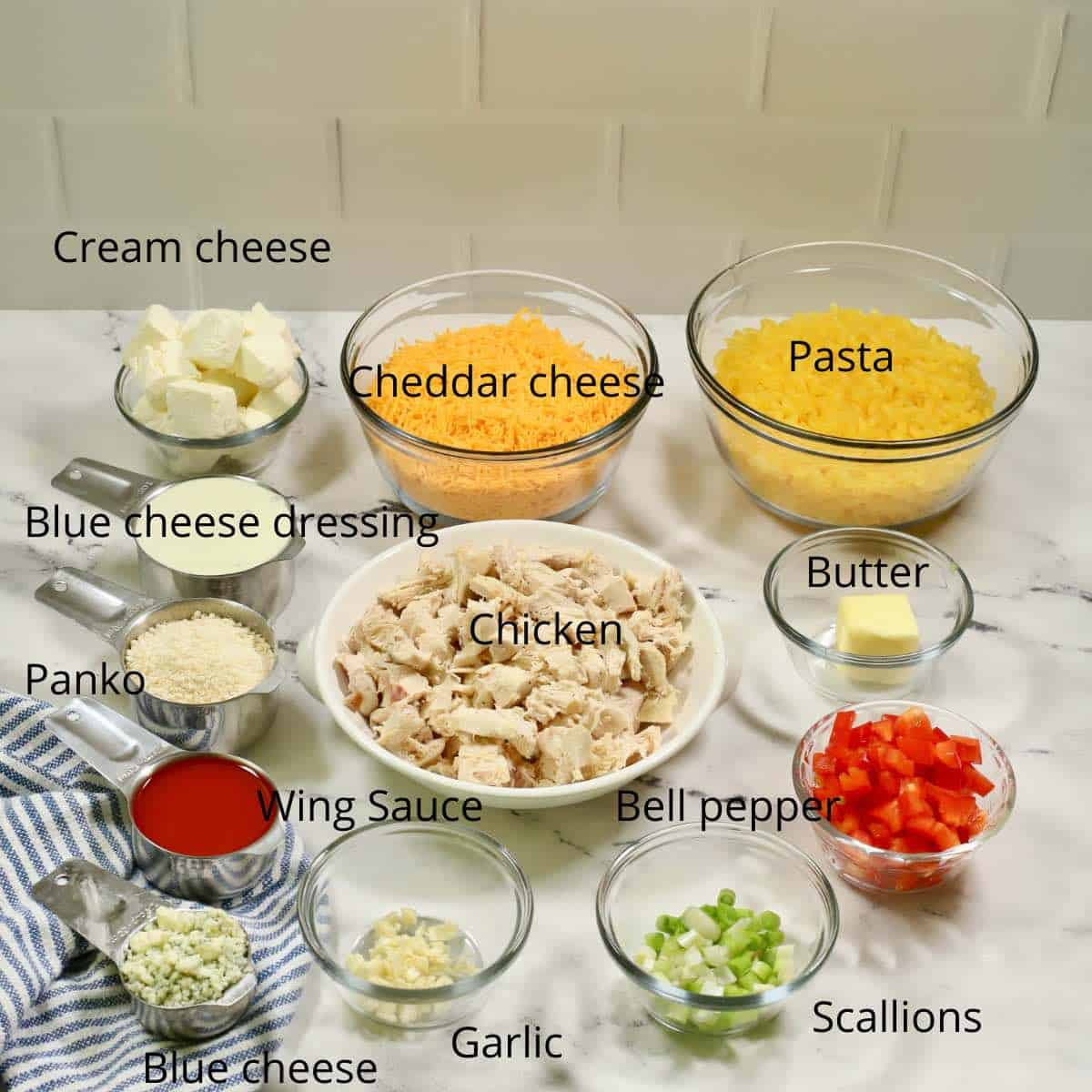 A large bowl of shredded chicken, pasta, cheese and other ingredients to make a chicken and pasta casserole.