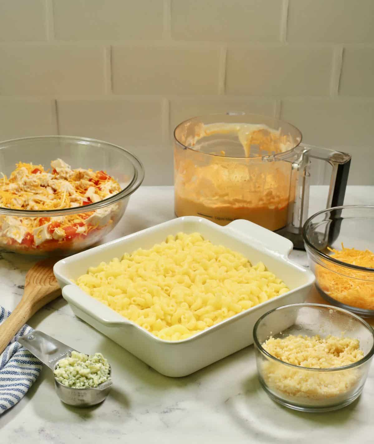 A square baking dish with pasta and a bowl of chicken and cheese.