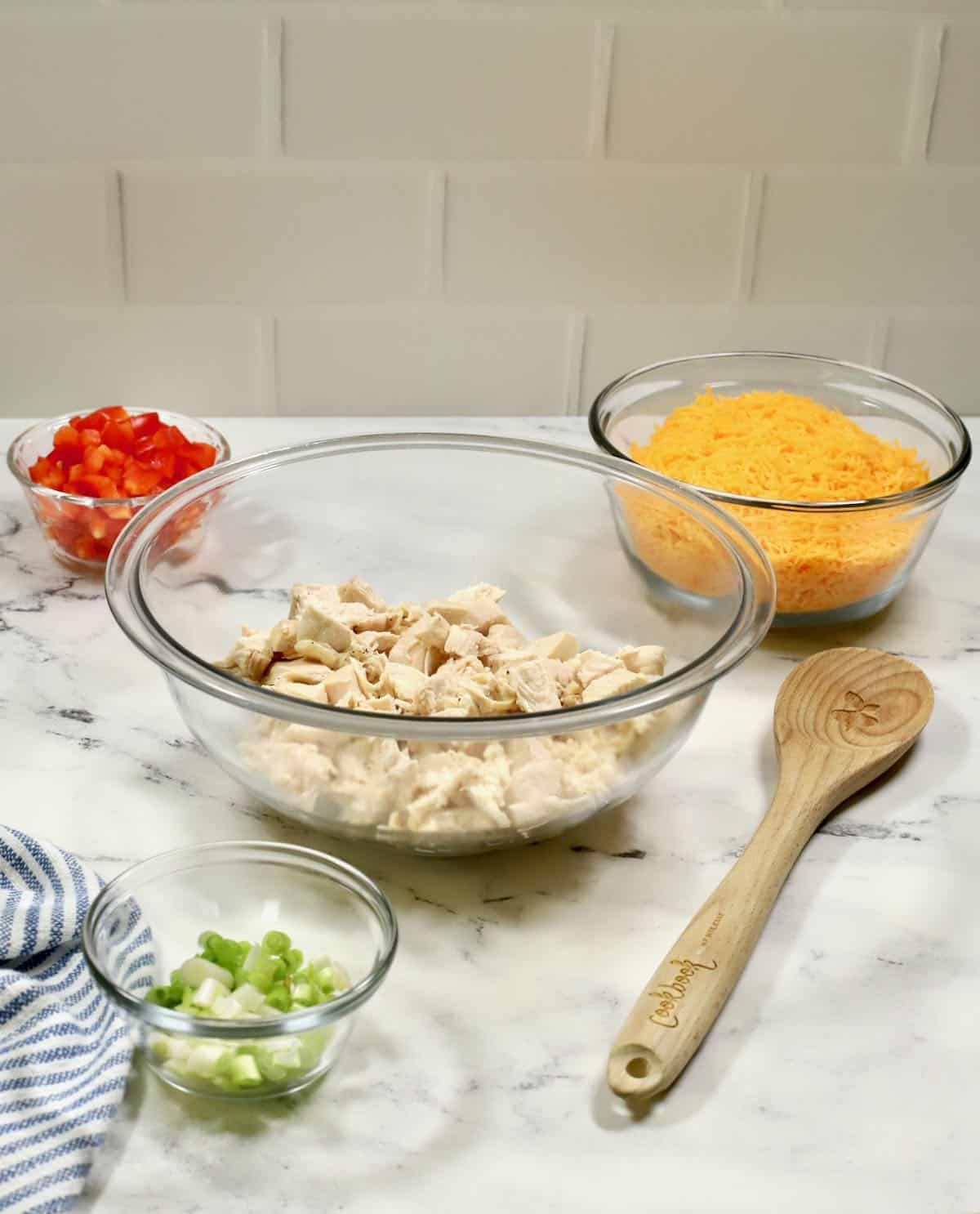 Chicken, cheese, and bell peppers in glass bowls.