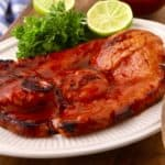 A grilled ham steak topped with apricot glaze on a white plate.