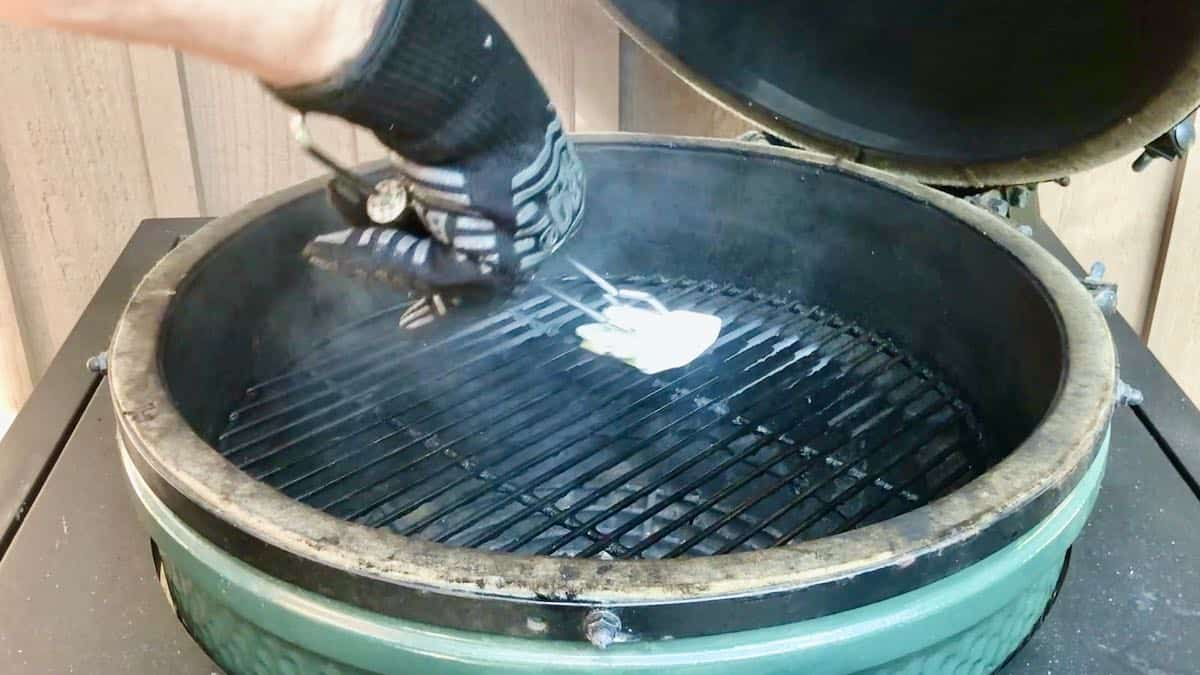 Oiling the grates of a grill with a folded up paper towel.