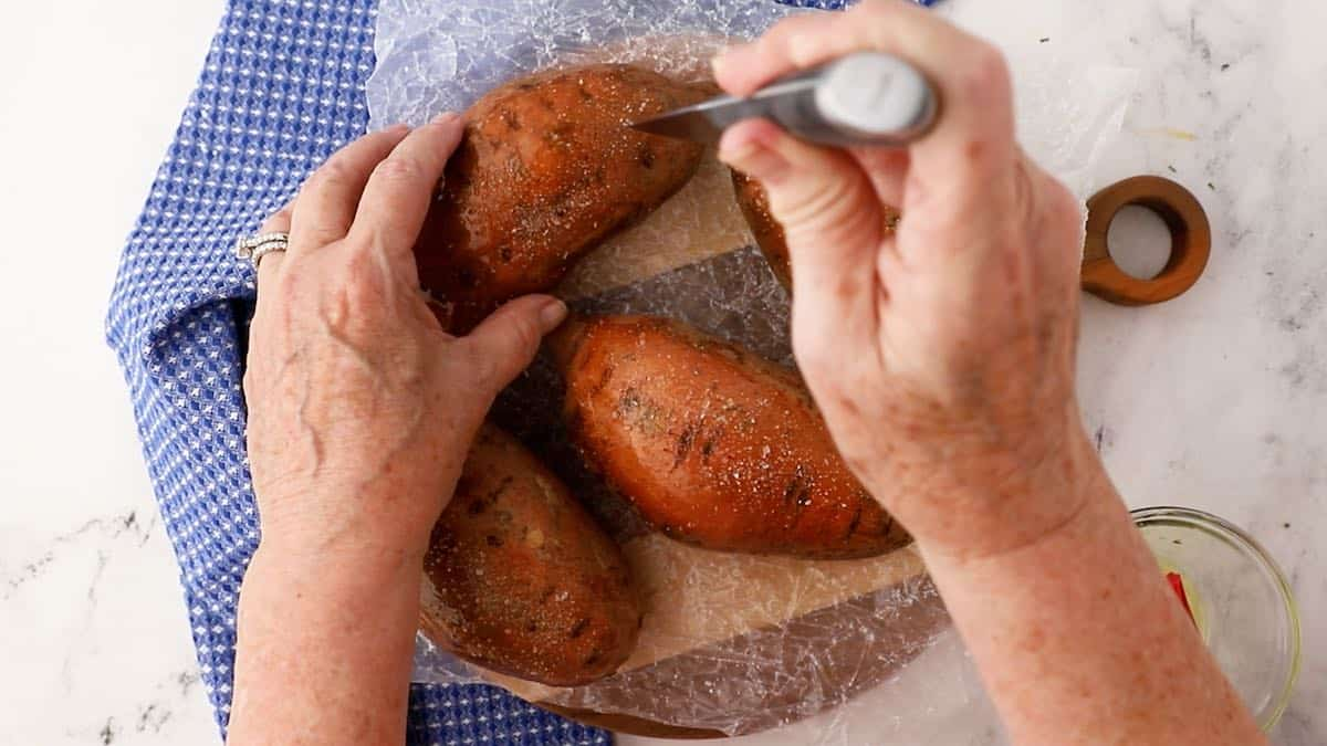 Using a paring knife to pierce holes in sweet potatoes prior to cooking.