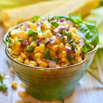 Fresh corn salad in a beautiful green pottery bowl.