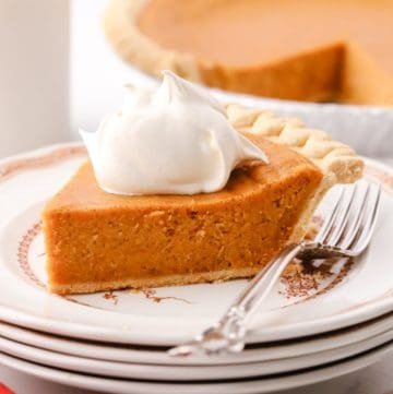 A slice of sweet potato pie topped with whipped cream on a plate.