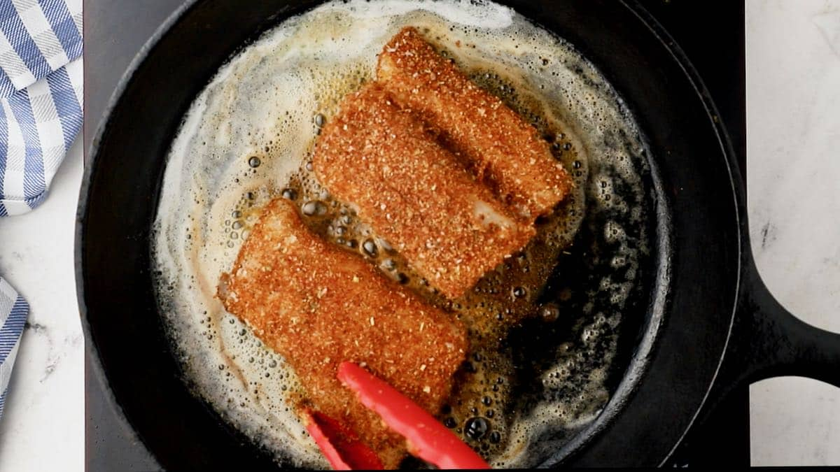 Two fish fillets cooking in a cast iron skiilet.
