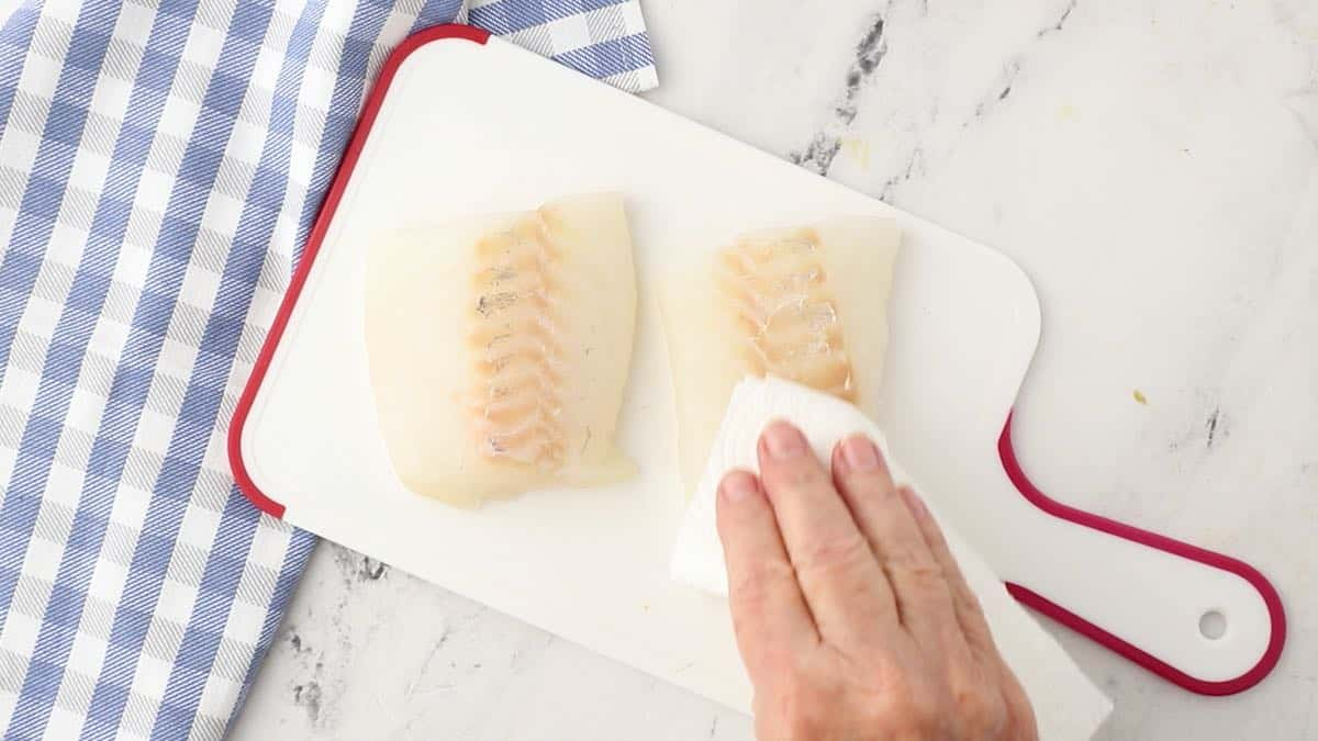 Using a paper towel to dry fish fillets.