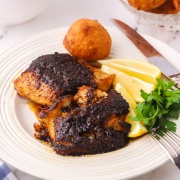 Two Blackened Cod fillets on a white plate.