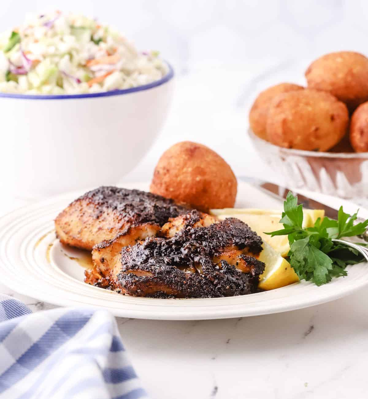 A white plate with blackened fish fillets.