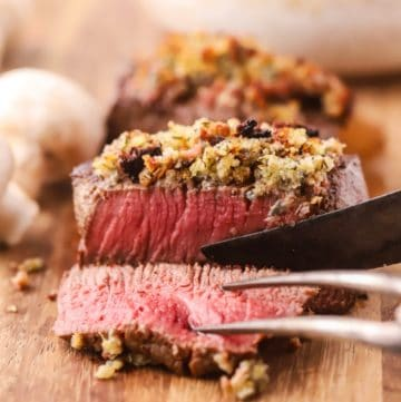 A filet mignon topped with blue cheese on a cutting board.