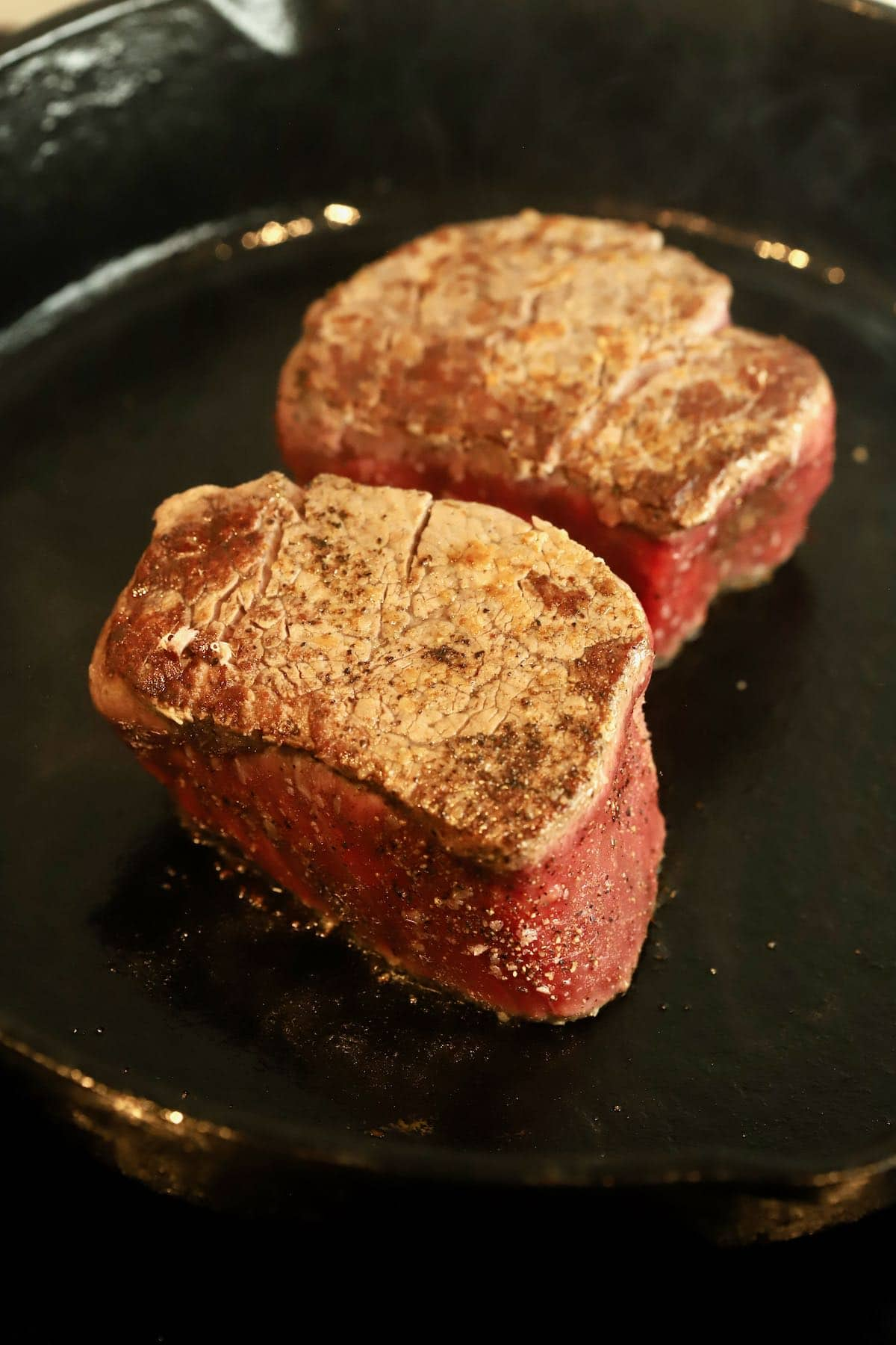 Two steaks cooking in a cast iron skillet.