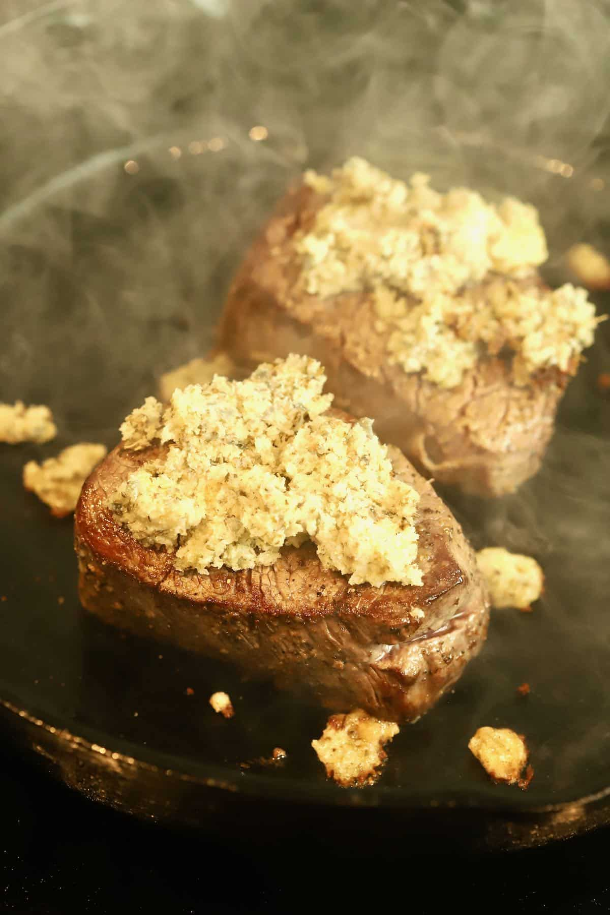 Two steaks topped with blue cheese cooking in a cast iron skillet.