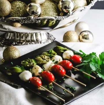 A black plate with five caprese skewers on it.