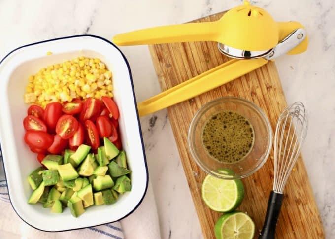 Dressing ingredients for Tomato Avocado Feta Salad on a cutting board.