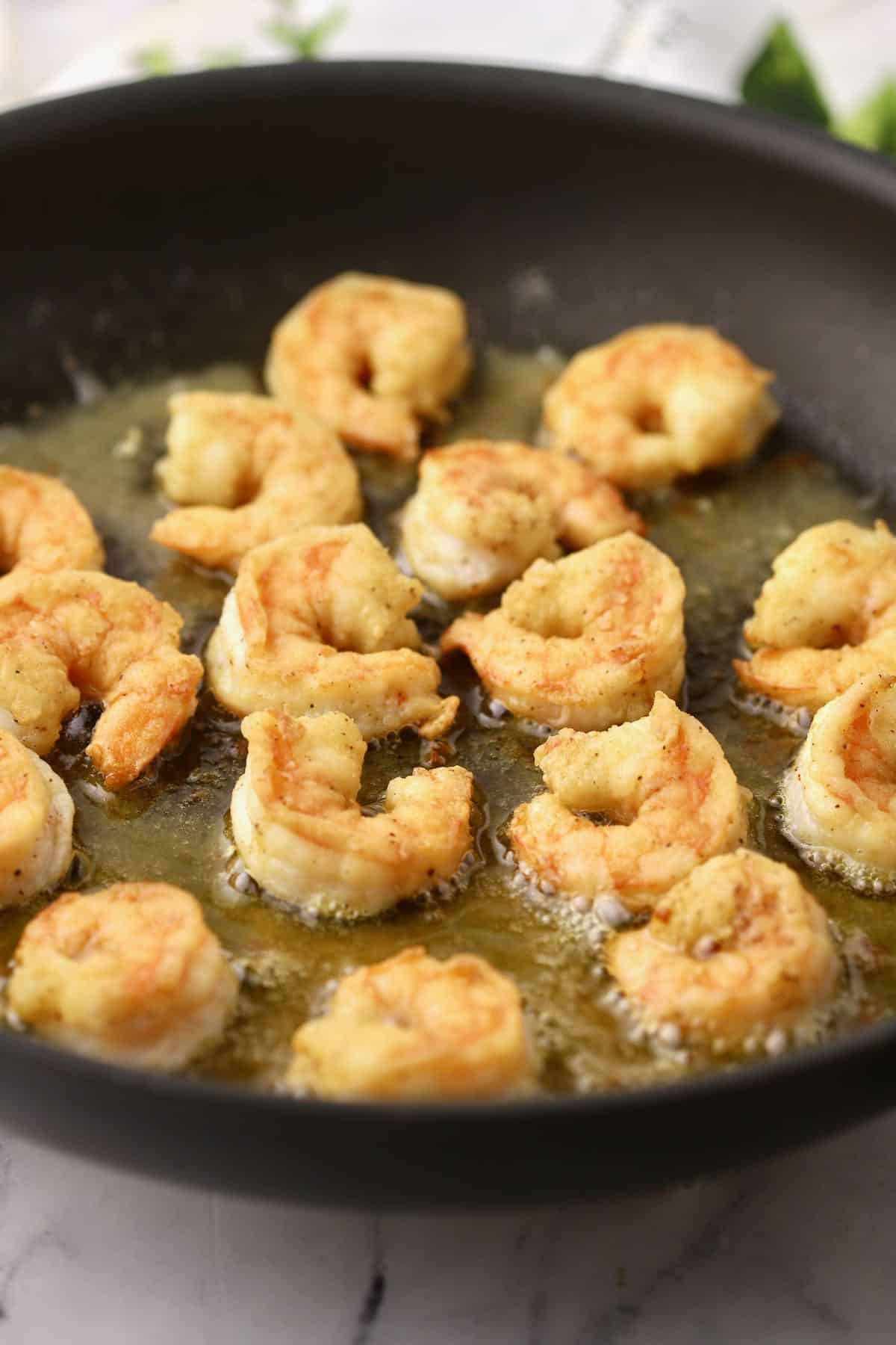 Fried shrimp cooking in a skillet.
