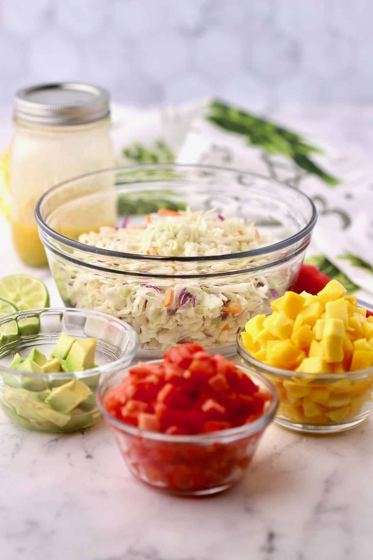 Coleslaw in a bowl with chopped mango and tomatoes.