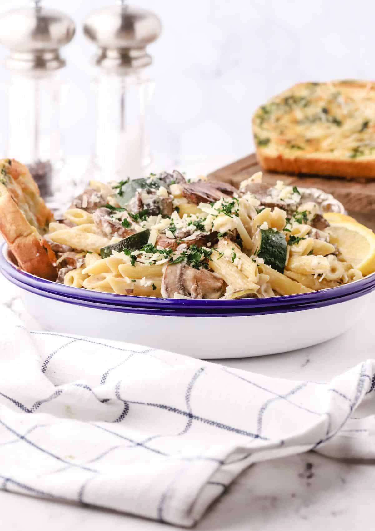 A blue and white bowl with mushroom zucchini pasta.