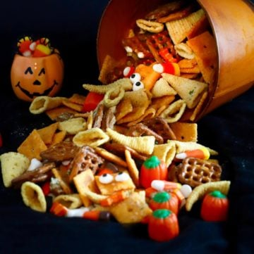 Bugles, candy corn, pretzels and nuts spilling out oof a orange bucket.