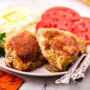 Two oven-fried chicken thighs on a plate with sliced tomatoes.