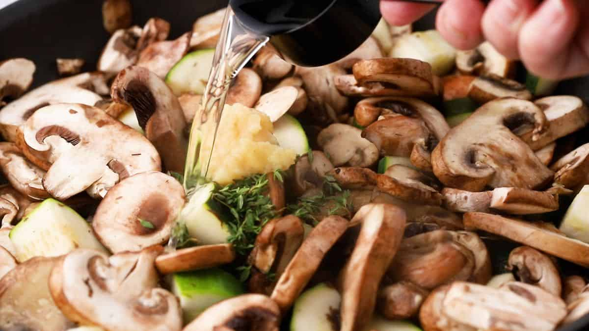 Adding wine to mushrooms and zucchini in a skillet.