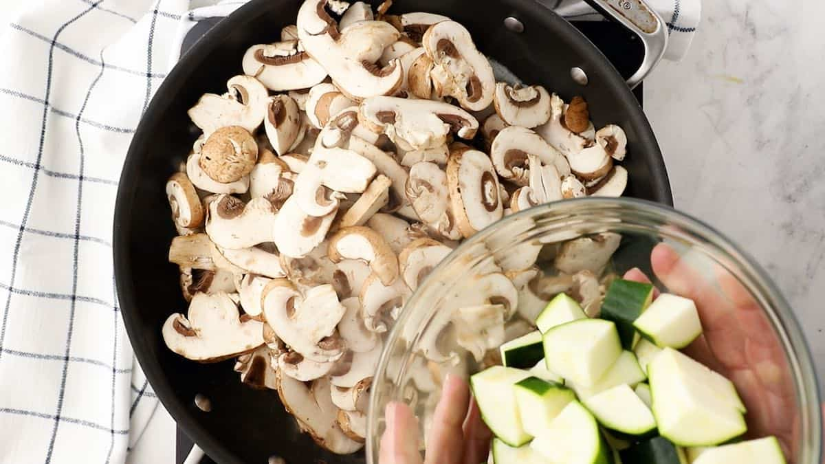 Adding mushrooms and zucchini to a skillet.
