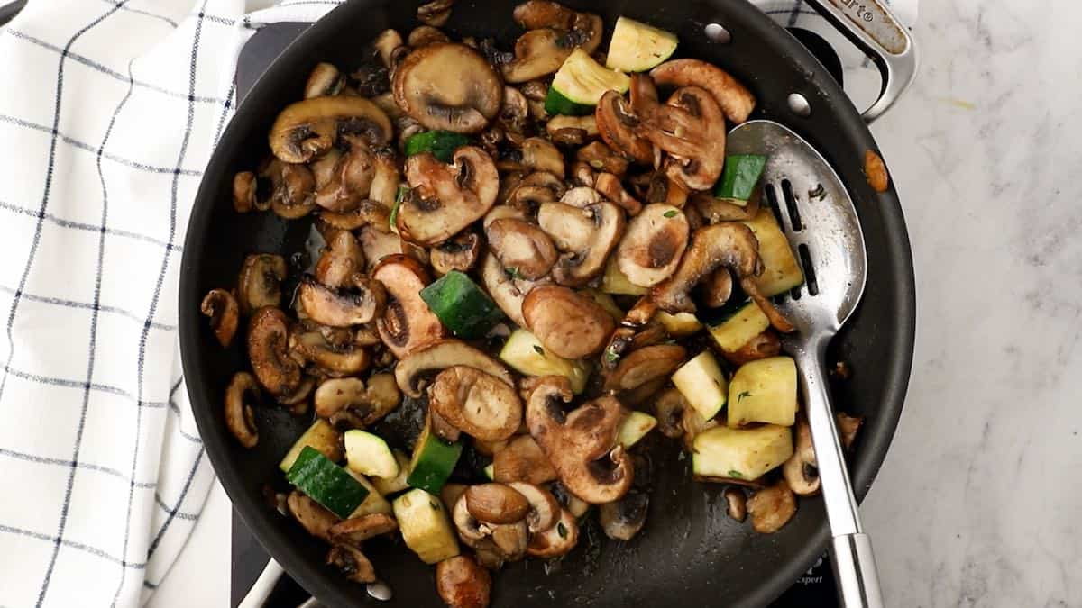 Cooked mushrooms and zucchini in a skillet.