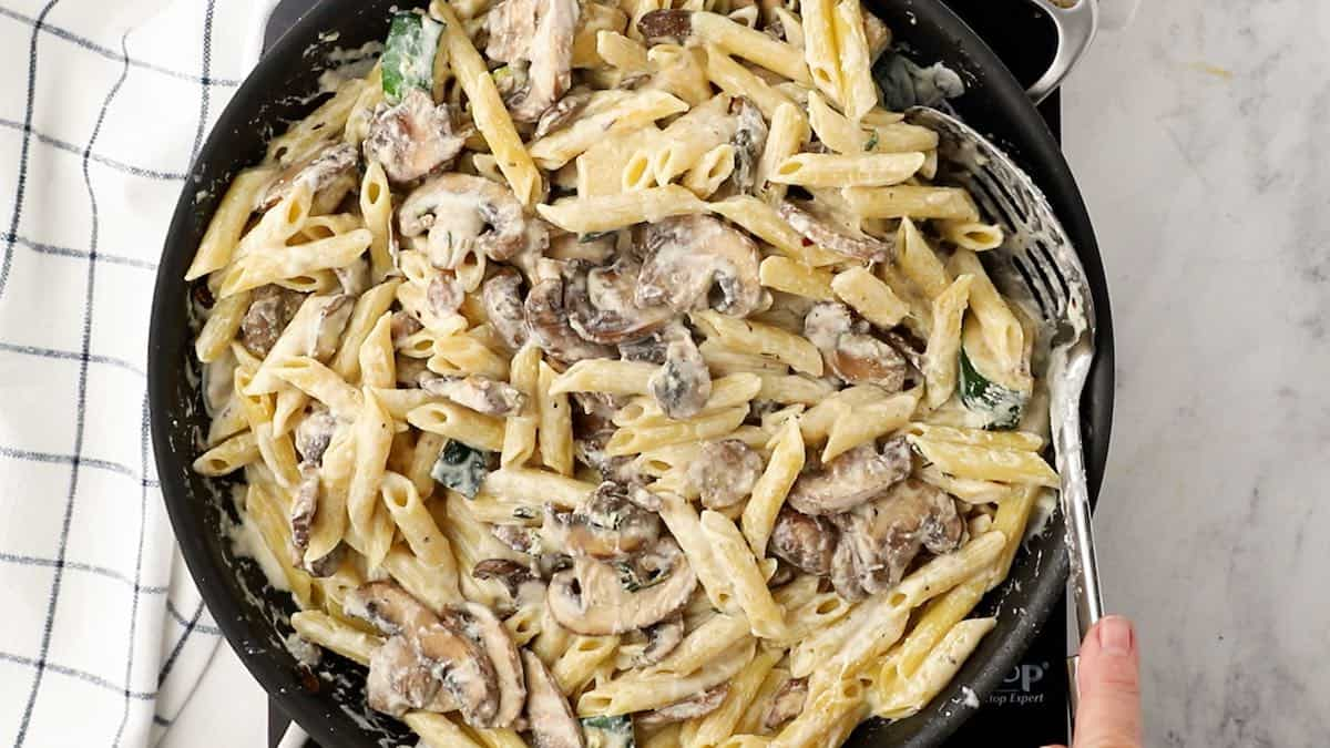 Combining pasta with veggies and cream sauce.